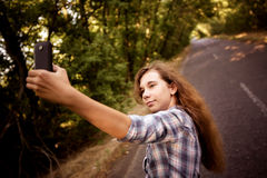 Beautiful teen girl making selfie on mobile phone Stock Images