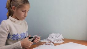 Beautiful teen girl painstakingly carves a snowflake out of paper. Beautiful teen girl painstakingly carves a snowflake out of white paper.Homemade decoration stock footage