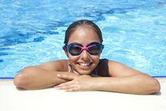 Beautiful teen girl in the pool looks at the camera from the water stock photo