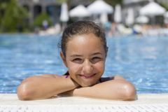 Beautiful teen girl in the pool looks at the camera from the water royalty free stock photography