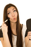 Beautiful teen girl pulling funny face applying blush Royalty Free Stock Images
