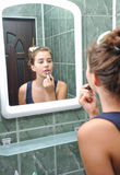 A beautiful teen girl putting lipstick and checking if she looks fine Stock Photography