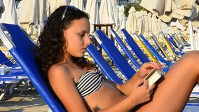Beautiful teen girl reading a book On The Beach stock video