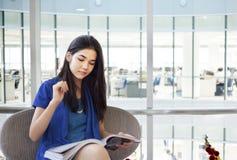 Beautiful teen girl reading magazine in office Royalty Free Stock Photo
