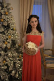 Beautiful teen girl in red dress smart. With embroidery and gifts inext to tree at Christmas Stock Photo