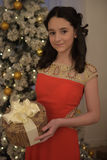 Beautiful teen girl in red dress smart. With embroidery and gifts inext to tree at Christmas Royalty Free Stock Photography