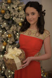 Beautiful teen girl in red dress smart. With embroidery and gifts inext to tree at Christmas Royalty Free Stock Images