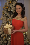 Beautiful teen girl in red dress smart. With embroidery and gifts inext to tree at Christmas Stock Photography