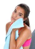 Beautiful Teen Girl Resting After Workout. Beautiful teen girl in workout clothes wiping face with towel after workout.  Sitting on workout bench looking towards Stock Photos