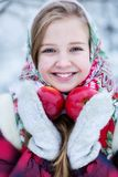 Beautiful teen girl in Russian national clothes with red apples in winter hands stock image