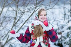 Beautiful teen girl in Russian national clothes with red apples in winter hands stock photo