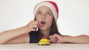 Beautiful teen girl in Santa Claus hat with an appetite and pleasure eating a birthday cake on white background Royalty Free Stock Image