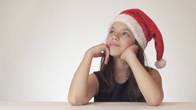 Beautiful teen girl in Santa Claus hat sitting and dreaming of a gift, expresses happiness and anticipation on white Royalty Free Stock Photography