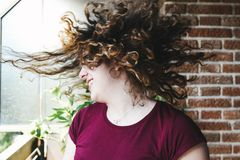 Beautiful teen girl shaking head with curly hair stock images