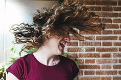 Beautiful teen girl shaking head with curly hair royalty free stock photo