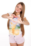 Beautiful teen girl shows a heart symbol Stock Photos
