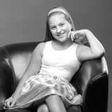 A teenage girl is sitting on a leather chair. Beautiful teen girl sits in the studio on a leather chair. Concept of youth fashion and culture Stock Image