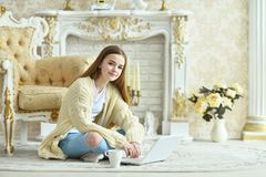Beautiful teen girl sitting on floor and using laptop Stock Images