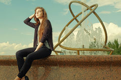 Beautiful teen girl is sitting on granite fountain. Urban outdoors, teenager's street lifestyle. Toned image. Stock Photography