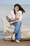 Beautiful teen girl sitting on log Royalty Free Stock Photography