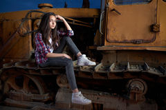 Beautiful teen girl sitting on an old tractor Royalty Free Stock Photo