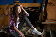 Beautiful teen girl sitting on an old tractor Royalty Free Stock Photography