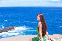 Beautiful teen girl sitting on rocky ledge over blue ocean Stock Photos