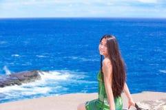 Beautiful teen girl sitting on rocky ledge over blue ocean. Beautiful biracial teen Asian Caucasian girl sitting on rocky ledge overlooking blue ocean off the Stock Photos