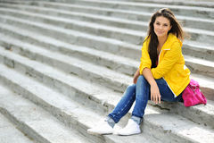 Beautiful teen girl sitting on a stairs in colorful clot Royalty Free Stock Image