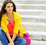 Beautiful teen girl sitting on a stairs in colorful clot Royalty Free Stock Photography