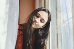 Beautiful teen girl sitting by the window royalty free stock photo