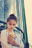 A beautiful teen girl stands on a background of modern buildings and holds a smartphone in her hands. royalty free stock photography