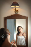 A beautiful teen girl studies her appearance as she looks into the mirror Royalty Free Stock Photography