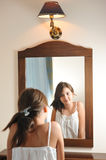 A beautiful teen girl studies her appearance as she looks into the mirror. At her beautiful young reflection. Teen girl happy with their appearance in the royalty free stock photo
