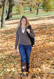 Beautiful teen girl walking in autumn leaves. Pretty young woman walking through bright fall leaves royalty free stock photography