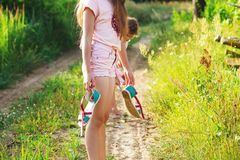 Beautiful teen girl is walking barefoot at sand road on warm sum. Mer day. Cute Girl feeling very happy on Summer background Stock Image