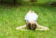 Beautiful teen girl in white dress lying on green grass. Boho style portrait. Text space stock images