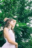 Beautiful teen girl in white dress top with plumeria tree. Boho style portrait Royalty Free Stock Photography