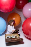 Beautiful teen girl with wooden abacus and a suitcase full of mo Royalty Free Stock Photos