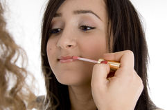 Beautiful teen having makeup put on her. Beautiful teen getting applied lipstick with brush on  an isolated white background Stock Photo