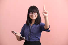 Beautiful teen holding tablet pointing finger Stock Photo