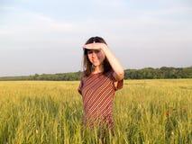Beautiful Teen Lady Looks in Field. Beautiful Teen Lady Looks from below hand in Field royalty free stock photos