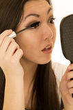 Beautiful teen model applying mascara holding hand mirror Stock Images