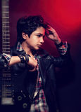Beautiful teen model. Portrait of attractive teen model posing with guitar in the studio over red background, beautiful guy with trendy hairdo wearing stylish Royalty Free Stock Images