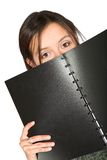 Beautiful teen peeping over notebook Royalty Free Stock Image