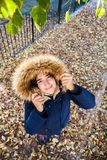 Beautiful teen poses with her coat among the autumn leaves in a sunny afternoon royalty free stock photography