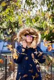 Beautiful teen poses with her coat among the autumn leaves in a sunny afternoon stock photography