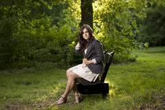Beautiful teen sitting on a bench in park Stock Photography
