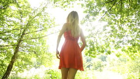 Beautiful teen spinning in the sunlight under the trees Stock Photo