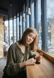 Beautiful teen student girl concentrated attention using smartphone for internet surfing at street cafe sitting near big window ho Royalty Free Stock Photography